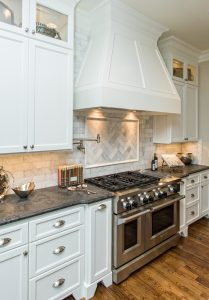 A beautiful white kitchen with marble backsplash and gas range in this custom built home in Greenville, SC.   GoodwinFoust.com  Custom Home Builder - Greenville, SC